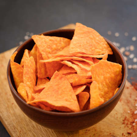 junk fast food and unhealthy eating. nacho tortilla chips in a bowl. crunchy triangular crisps in a bowl. Stock Photo