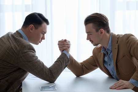business competition and rivalry.  arm wrestling fight for superity. focused serious men clenching hands
