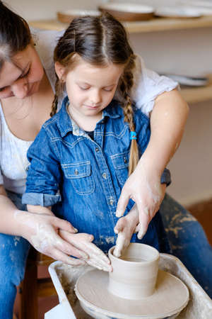 pottery workshop. handmade craft. artisan teaching a child girl how to form and shape clay on potter wheel