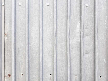 profiled metal sheet silvery background. industrial abstract design. vertical stripes. weathered dented surface with holes and rivets. copyspace concept