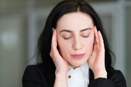 headache stress tiredness concept. woman massaging her temples. face portrait of young business brunette lady Stock Photo