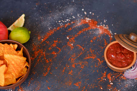 salsa tomato sauce and nacho chips on dark background with flecks of salt and powdered red pepper or paprika. food and culinary condiments. spices mix on rough textured surface. free space concept