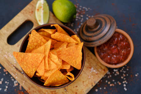 junk fast food and unhealthy eating. nacho tortilla chips in a bowl. crunchy triangular crisps in a bowl with salsa sauce on dark background