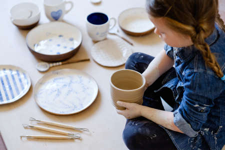 child hobby. creative pottery leisure. artistic kid upbringing. little girl and assortment of handmade craft clay crockery Stok Fotoğraf