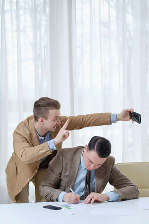 annoying intrusive coworker taking selfie with a busy colleague in office. business and work ethics Banque d'images