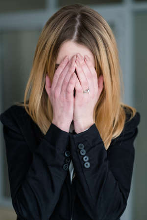 emotion concept. sad distraught woman covering her face with hands. crying business lady in office workspace. bad news 写真素材 - 103352756