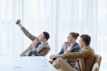 selfie time. social network addiction. life oversharing lifestyle. business men taking photos of themselves in the office Foto de archivo - 103753146