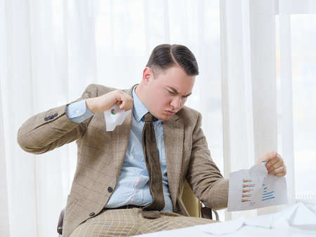 angry disappointed business man tearing documents to pieces. deal failure or money loss concept
