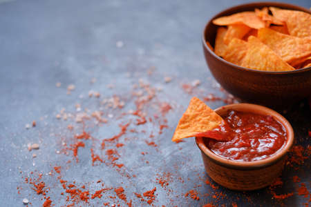 crispy crunchy tortilla nacho chips are a great party munchies. delicious food snack. triangular crunchy slice dipped in salsa tomato sauce Stock Photo