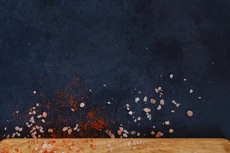 dark background with scattered chunks of salt and red pepper or paprika spice condiments. rough textured surface. food preparing and cooking concept