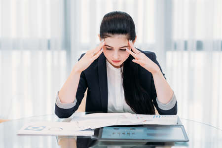 stressed tired office woman. young business lady overwhelmed with work. beautiful girl sitting in office her head in hands Stock Photo