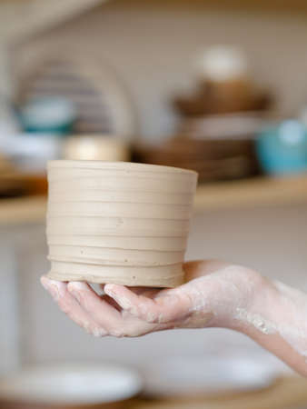 handmade hobby pottery courses. master class at workshop. potter holding a craft clay jug