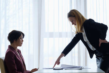 boss scolding her employee. business woman getting a reproof from chief manager. superior and subordinate professional relationship. Stock Photo