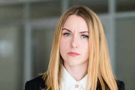 emotion face. woman with a quizzical interrogatory inquiring look. business lady at office workspace. young beautiful blond girl portrait