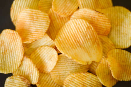 fast food. waved ridged chips recipe. golden fried spicy potato slices mix background