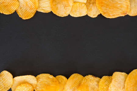 chips food background. wavy ridged potato crisps mix. salty spicy crunchy slices frame on dark background