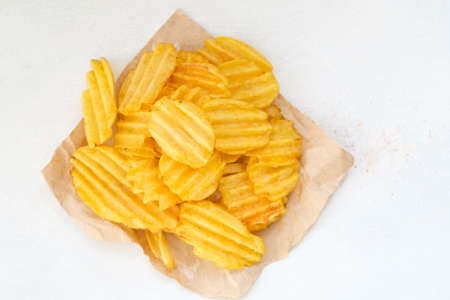 crispy crunchy potato chips are a great party munchies. delicious food snack. waved rudged fried slices on white background 版權商用圖片