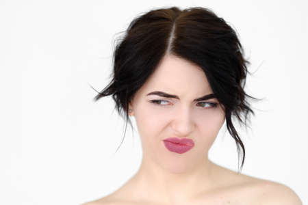 emotion face. discontent dissatisfied envious woman looking sideways and thinking. young beautiful brunette girl portrait on white background. Stock Photo