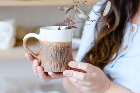 pottery craftsman. artistic hobby or handicraft vocation. creative profession concept. hands holding a craft clay mug with a plant in it Imagens