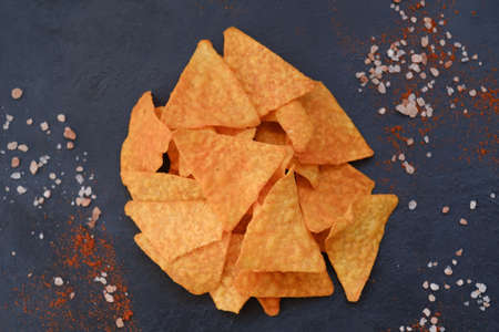 junk fast food and unhealthy eating. nacho tortilla chips. crunchy triangular crisps on dark background Stock Photo