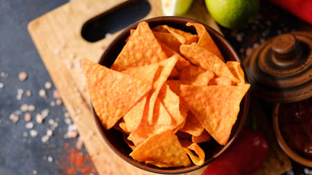 crispy crunchy tortilla nacho chips are a great party munchies. delicious food snack. fried triangular slices in a bowl