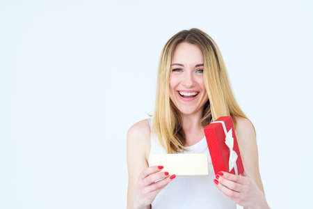 joyful smiling young woman with present in a red gift box. unexpected nice surprise. festive occasion greeting and holiday celebration concept