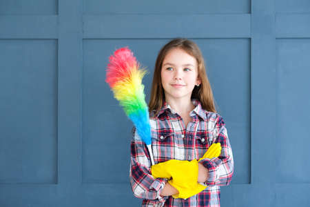 moms little helper. cute girl in yellow rubber gloves and with rainbow duster is ready for her domestic chores and housework