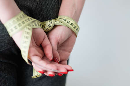self control will power and restraint. dieting weightloss and fitness. woman hands tied with measuring tape behind her back