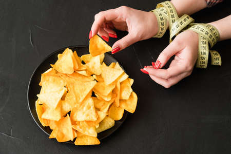 unhealthy fast food snacks. bad nutrition habits. woman breaking her diet eating chips