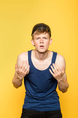 defiance and arrogance. cocky and aggressive man. bullish thug in a tank top. portrait of a young guy on yellow background. emotion facial expression. feelings and people reaction.