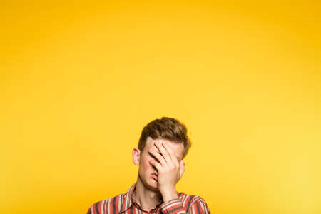 facepalm. ashamed abashed man covering his face with hand. portrait of a young guy on yellow background popping up or peeking out from the bottom. copy space for advertising. Фото со стока
