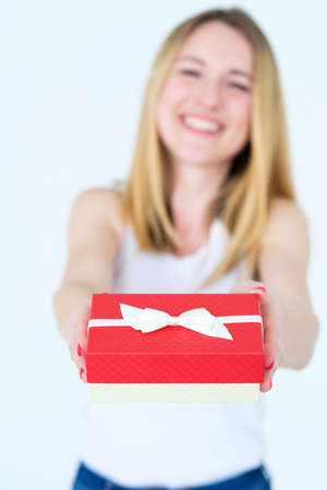 red gift box in womans hands. holiday present or happy anniversary reward for a loved one.