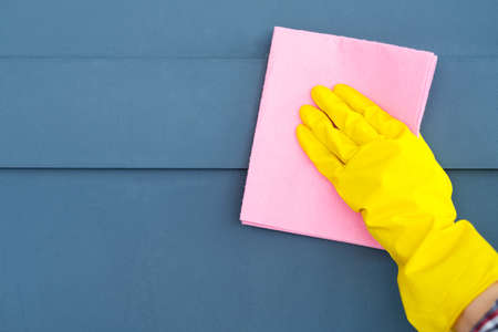 house hygiene and home cleaning. hand in yellow protective rubber glove wiping the surface Stock Photo