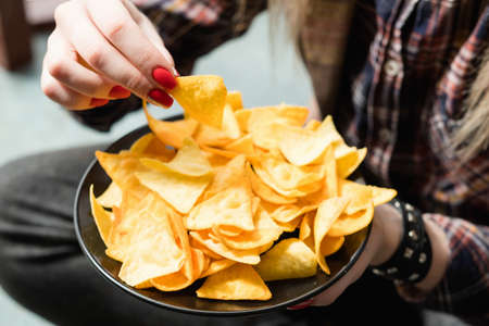 junk fast food and unhealthy nutrition. woman eating chips from a bowl of crunchy crisps