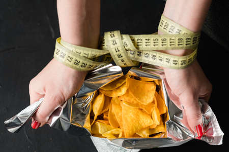weightloss and slimming. crispy chips food temptation. body size and fitness. woman hands tied with measuring tape