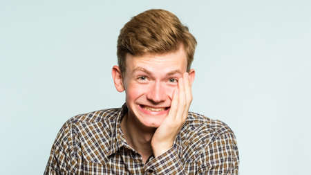 happiness enjoyment and laugh. man with a wide grin. portrait of a young guy on light background. emotion facial expression. feelings and people reaction.