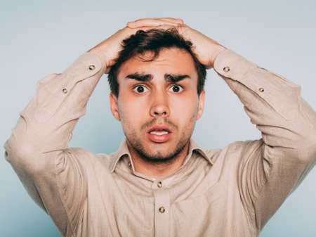oh no. terrified shocked desperate alarmed dismayed man clutching his head. portrait of a young brunet guy on light background. emotion facial expression. feelings and people reaction concept.