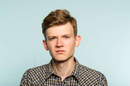 man with a scornful disdainful disrespectful look. portrait of a young guy on light background. emotion facial expression. feelings and people reaction concept.