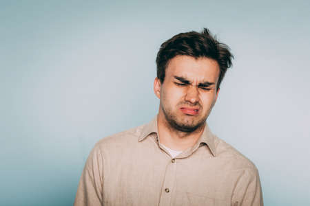 nausea aversion repulsion. reluctant man grimacing in disgust. portrait of a young brunet guy on light background. emotion facial expression. feelings and people reaction concept. Stock Photo