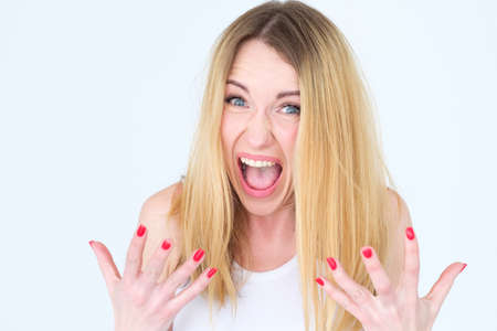 emotion face. cross angry shocked enraged woman screaming with disbelief. young beautiful blond girl portrait on white background. Reklamní fotografie