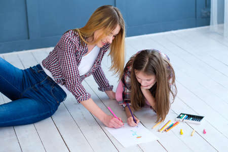 loving family relationship. mothers involvement in kids hobby. mom and daughter drawing together at home.