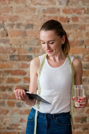 slim and fit body is every girls dream. weight insecurity and desire to have a perfect figure. woman reading diet plan and holding a glass of water