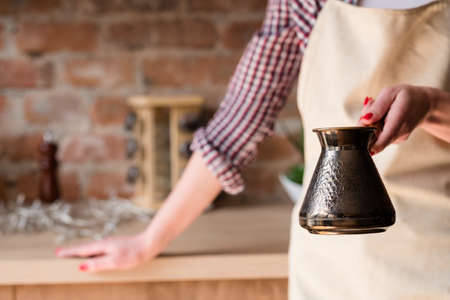 morning coffee tradition. caffeine addiction. strong hot beverage freshly brewed in a jezve or turkish pot in woman hands Stock Photo