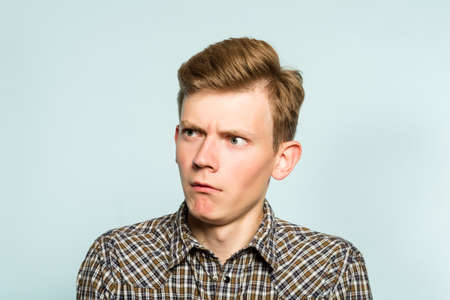 amazed astonished shocked dazed impressed stunned man looking sideways. portrait of a young guy on light background. emotion facial expression. feelings and people reaction. Stock Photo