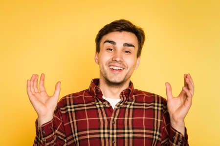 discount is this big. happy smiling joyful man with his hands in the air. portrait of a young handsome brunet guy on yellow background. emotion facial expression. feelings and people reaction concept. Banco de Imagens