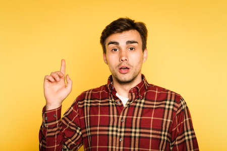 look up. amazed shocked man with open mouth pointing upward. portrait of a young handsome brunet guy on yellow background. emotion facial expression. feelings and people reaction concept.