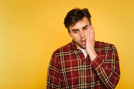 shocked gobsmacked stressed man. clutching his face. feelings of regret remorse and dismay. portrait of a brunet guy on yellow background. emotion facial expression. feelings and reaction concept.