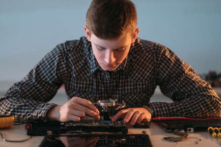 electronic renovation in repair shop. engineer working with disassembled motherboard Stock Photo