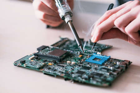 electronic renovation in repair shop. engineer soldering computer motherboard