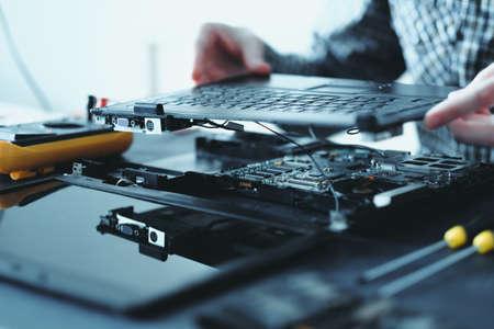 elektronische Renovierung in der Werkstatt. Ingenieur zerlegt kaputten Laptop entfernt Tastatur Standard-Bild